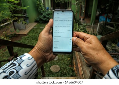 A contributor is marking photos uploaded to Shutterstock as an editorial in Bekasi, West Java, Indonesia, on July 20, 2019.