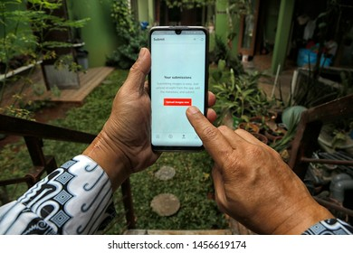 A contributor is uploading photos to Shutterstock in Bekasi, West Java, Indonesia, on July 20, 2019.