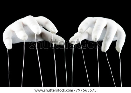 Control concept, hands in white gloves with ropes on a black background