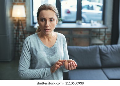 Control health. Focused mature woman sweating and calculating heartbeat
