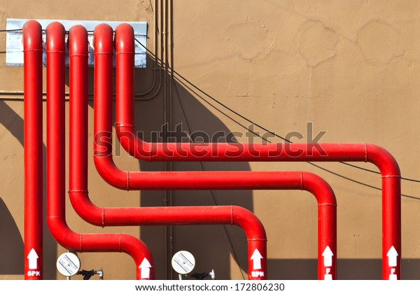 Control panel of red water pipes outside building of sprinkler fire alarm system on brown concrete wall