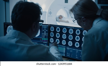 In Control Room Doctor and Radiologist Discuss Diagnosis while Watching Procedure and Monitors Showing Brain Scans Results, In the Background Patient Undergoes MRI or CT Scan Procedure.