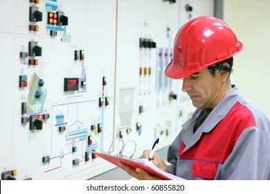 Control Room Engineer. Power Plant Control Panel. Engineer standing in front of the control panel in the control room and write the results of the measurements.