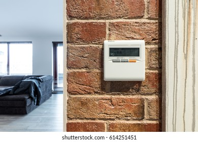 Controller for warm floor system, on a brick wall.