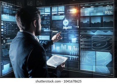 Controlling everything. Calm clever attentive programmer pointing to the transparent screen while holding a convenient tablet and checking the information