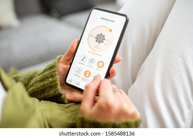 Controlling home conditioning with a smart phone, close-up. Concept of a smart home and mobile application for managing smart devices at home