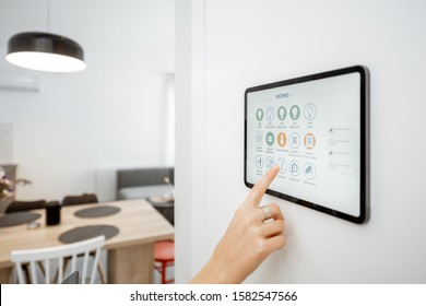 Controlling home with a digital touch screen panel installed on the wall. Close-up on a screen with mobile application for managing smart devices