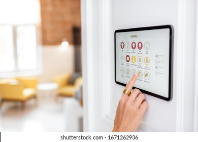 Controlling home with a digital touch screen panel installed on the wall in the living room. Concept of a smart home and mobile application for managing smart devices at home