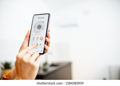 Controlling home ventilation or conditioning with a smart phone, close-up. Concept of a smart home and mobile application for managing smart devices at home