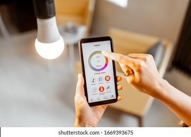 Kontrolle der Temperatur und Intensität der Glühbirne mit einer Smartphone-Anwendung. Konzept eines intelligenten Zuhause und Lichtmanagement mit mobilen Geräten