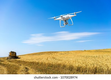Controlling a remote helicopter drone. Drone flying over fields