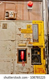 Controls, phone, and alarm bell. Freight elevator inside an abandoned factory.