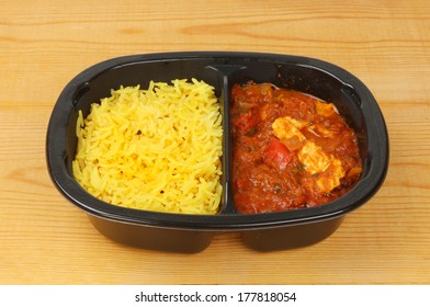 Convenience meal of chicken curry and rice in a plastic carton on a wooden worktop