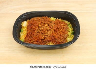 Convenience meal, lamb biryani, in a plastic tray on a wooden tabletop