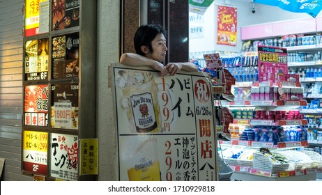 A convenience store Japanese merchant is standing behind a beer & alcohol sign and dreams, October 23rd, 2019, Japan.