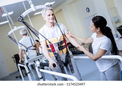 Convenient construction. Optimistic aged disabled patient looking glad while wearing a special helpful body vest with a cheerful attentive worker of a rehabilitation center holding his hand