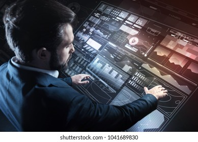 Convenient screen. Calm serious responsible programmer looking careful while standing in his elegant suit and slowly touching the icons on a futuristic transparent screen