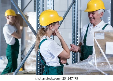 Conversation between young woman and her older colleague in warehouse