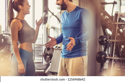 Conversation and laughter after a day at the gym. Happy and smiling sports couple talking in gym.