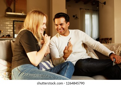 Conversation on sofa of young family couple at home apartment.