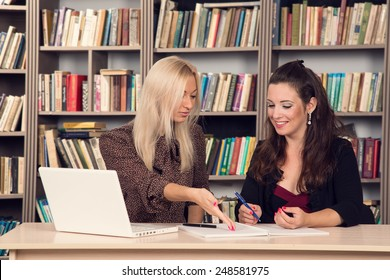 Conversation women office. Two young businesswomen having a meeting in the office sitting at a desk having a discussion with focus. Two girls students discuss course material. Work on the computer.