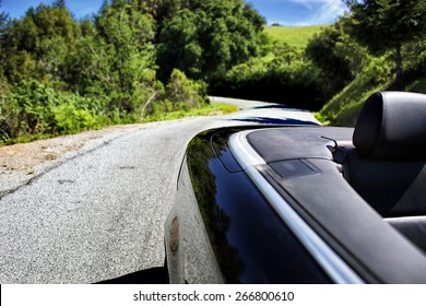 Convertible Car Driving on a Winding Road on a sunny summer day