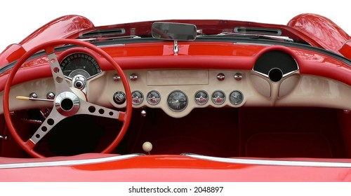 The convertible top is down in the horizontal view of the white dashboard of vintage red sportscar.  All the gauges and the steering wheel are in beautifully maintained or restored condition.