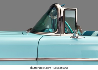 Convertible windshield and drivers seat. side view of a aqua blue classic car's windscreen and steering wheel. isolated on gray.