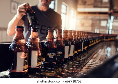 Conveyor with beer bottles moving in brewery factory. Young man supervising the beer bottling process and checking the quality at the manufacturing plant.