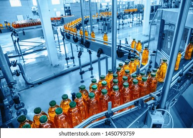 Conveyor belt, juice in bottles on beverage plant or factory interior in blue color, industrial production line, toned