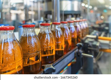 Conveyor belt, juice in bottles on beverage plant or factory interior, industrial production line, selective focus. - Shutterstock ID 1667345260