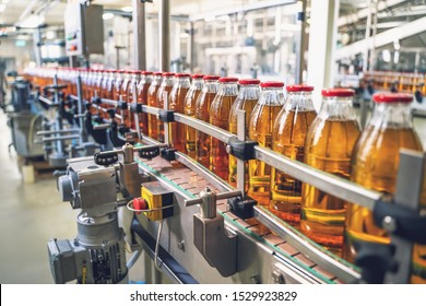 Conveyor belt, juice in glass bottles on beverage plant or factory interior, industrial manufacturing production line, toned - Shutterstock ID 1529923829