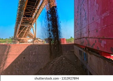 Conveyor belt loading bauxite aluminum ore into a capesize bulk carrier ship at a river bank jetee in the Kamsar, Guinea, West Africa.