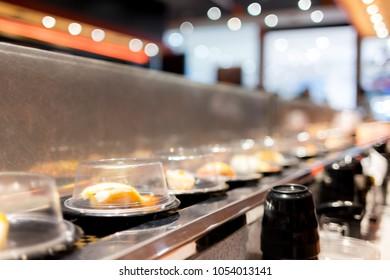 Conveyor belt sushi in japan restaurant  with blurred background.