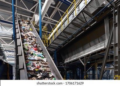 Conveyor belt transports garbage inside drum filter or rotating cylindrical sieve with trommel or sorting pieces of garbage into various sizes fractions at recycling plant