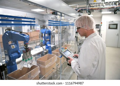 Conveyor belt worker operates a robot that transports insulin bags - modern factory for the production of medicines in the healthcare sector