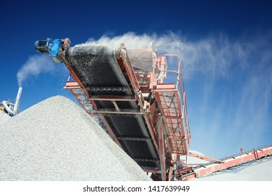 Conveyor belt of a working mobile crusher, close-up, with blown away by the wind white stone dust against a blue sky.