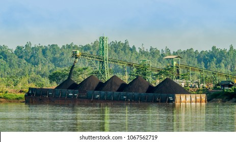 conveyor loading the barge with black coal from the stockpile on the riverbank.  Upper mahakam, Outback of Borneo, Indonesia