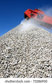 Conveyor and pile of quarry stone for building sorted according to size