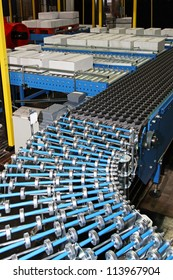 Conveyor rollers at box packing line in factory