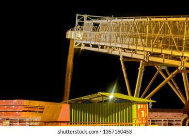 A conveyor transports bauxite, which is refined into aluminum, from an storage area into a capesize bulk carrier ship at a river bank jetee at night in the Kamsar, Guinea, West Africa.