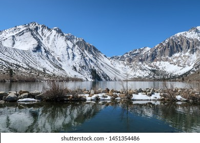 Convict Lake landscape of water, plants and snow-dappled mountains in California