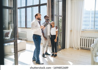 Convincing bearded man in formal outfit with clipboard showing ceiling to smiling embracing ethnic couple while standing at spacious sunny apartment