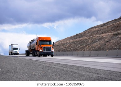 Convoy of the different make and models big rigs semi trucks with tank and dry van semi trailers driving on the road between hills in Oregon to delivery long haul commercial cargo to business partners