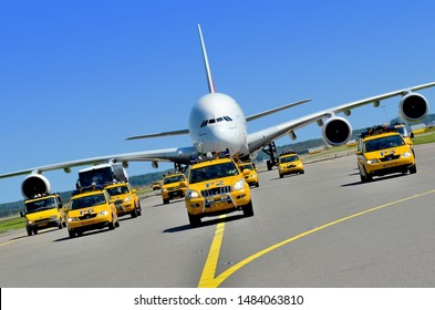 Convoy of yellow airport vehicles welcoming the largest commercial airplane in the world celebrating the first flight to Amsterdam. View from in front. (01/08/2012 - Amsterdam Schiphol, Netherlands)