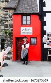 Conway, North Wales. May, 18, 2014: Woman standing dressed in traditional Welsh Costume smiling and posing for tourists outside the smallest house in Britain