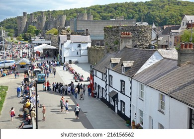 Conwy, Wales - May 26, 2013. Tourists on the quayside and outside the Smallest House in Great Britain in Conwy, Wales. The town is a popular tourist destination including the 13th century castle.