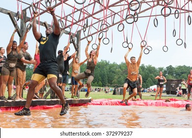 CONYERS, GA - AUGUST 22:  Competitors try to cross a muddy pool of water by swinging from rings at an amateur obstacle course race open to the public on August 22, 2015 in Conyers, GA.