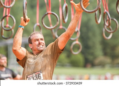 CONYERS, GA - AUGUST 22:  A man swings from rings suspended from wood beams to keep him out of water at an amateur obstacle course race open to the public on August 22, 2015 in Conyers, GA.