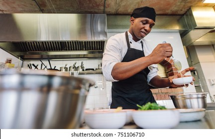 Cook adding sauce in bowl at commercial kitchen. African male chef cooking food in restaurant kitchen.